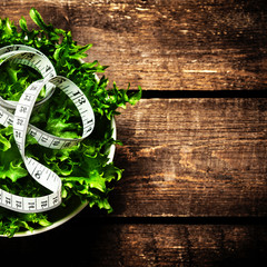 Weight Loss Salad and measuring tape over wooden background.  Di
