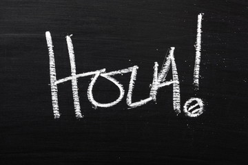 The Spanish word Hola written on a blackboard