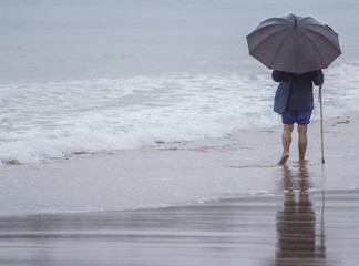 Anciano con paraguas paseando por la playa