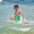 child splash jumping into the sea on the beach