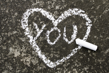 """heart with the word """"you"""" drawn in chalk on concrete"""