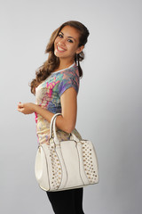 Dark beautiful girl in a trendy style with a white bag.