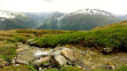 Cascade on small mountain stream in Alps, stream in meadow