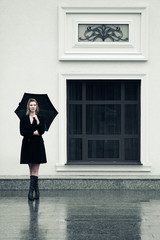 Happy fashion woman with umbrella in the rain