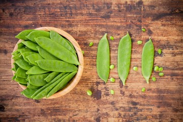 young pods of green peas on a wooden background