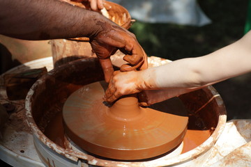 Hands of potters on a wheel
