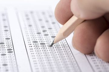 Male hand filling out multiple choice test with pencil