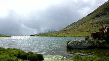 Silhouettes of lake banks in Alpine mountains, heavy dark clouds