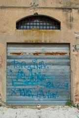Saracinesche grigio zincane, vecchia con graffiti