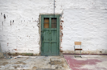 old white brick wall with green door