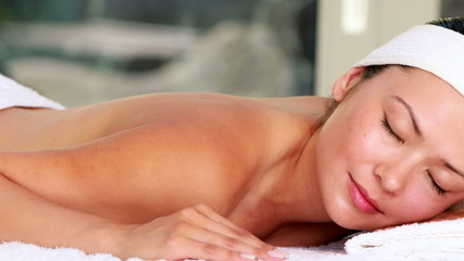 Beautiful brunette lying on massage table with eyes closed