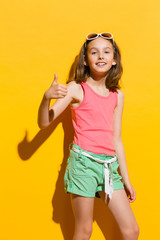 Smiling girl showing thumb up
