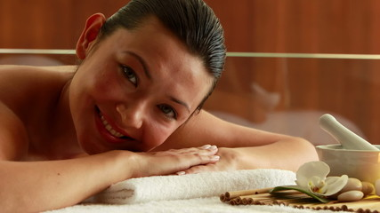 Gorgeous brunette lying on massage table smiling at camera