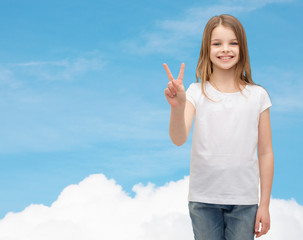 little girl in white t-shirt showing peace gesture