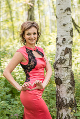 Smiling woman in pink dress walking in a birch forest