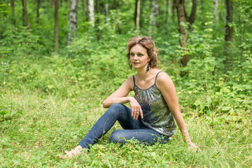Barefoot girl sitting in the birch forest