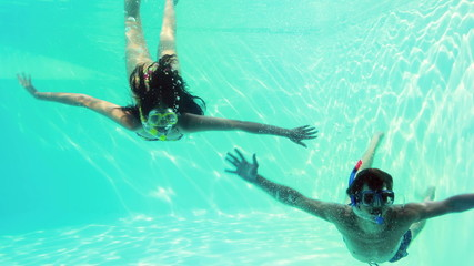 Happy couple jumping in swimming pool together wearing snorkels