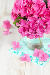 hydrangea flower in vase on wooden surface