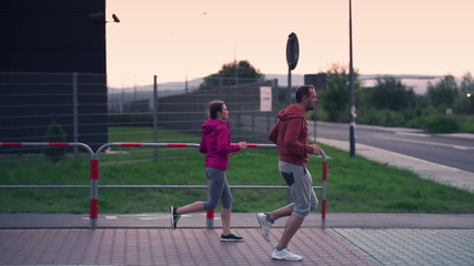 Young sporty couple jogging in the city in the evening