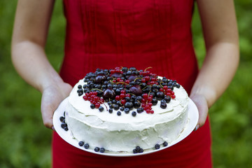 Holding a fresh berry cake