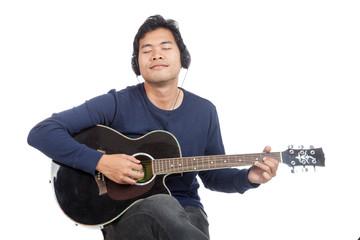Asian man playing guitar with headphone