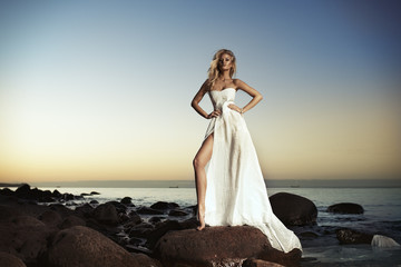 Sexy blond girl posing on a beach in white dress