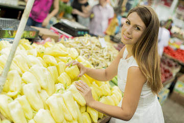 Young woman buying vegetables on the market