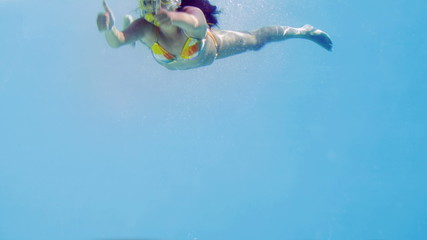Brunette jumping into swimming pool wearing snorkel
