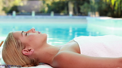Peaceful blonde lying on massage table poolside