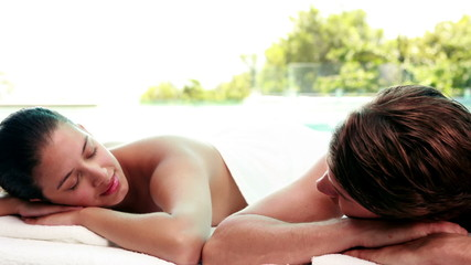Peaceful couple getting hot stone massages