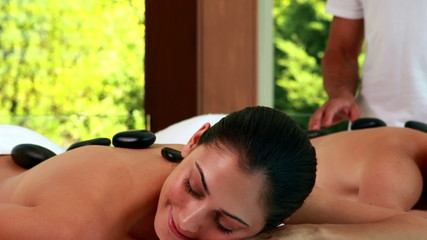 Relaxed friends enjoying hot stone massages