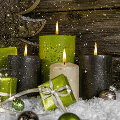 Weihnachten: Vier brennende Adventskerzen in Grün und Braun