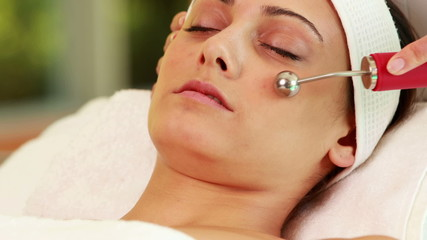 Pretty brunette getting micro dermabrasion treatment
