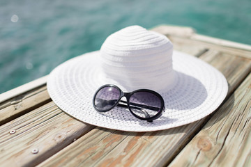 close up of hat and sunglasses at seaside