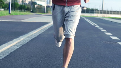 Jogger running on asphalt road in city, super slow motion