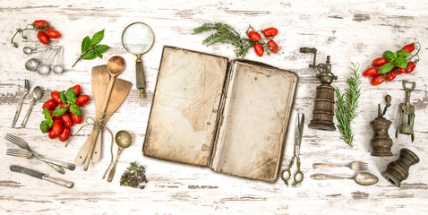 Old cookbook with vegetables, herbs and vintage kitchen utensils