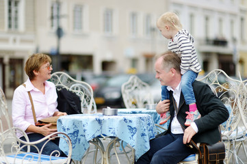Grandparents and their grandchild in outdoor cafe