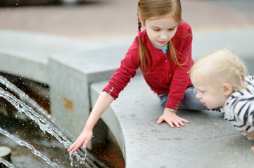 Two little sisters playing with a city fountain