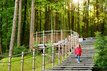 Adorable girl walking down stairs in summer park