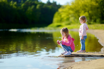 Two little sisters playing by a river