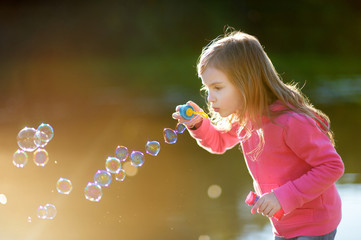 Funny lovely little girl blowing soap bubbles
