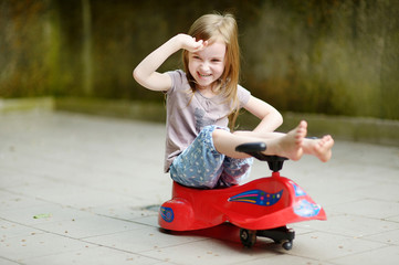 Adorable little girl driving a toy car