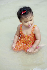 Asian baby first tasting the sea