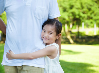 pretty little girl hug father waist in the park