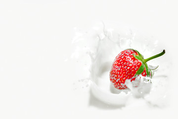 Red strawberry falling into the milky splash