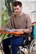 A disabled man sitting and ironing shirt