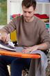 Disabled man ironing shirts at home
