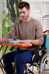 A disabled man sitting and ironing shirt