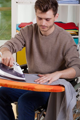 Disabled man ironing shirts at home