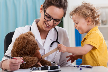 Doctor and little boy examining a teddy bear
